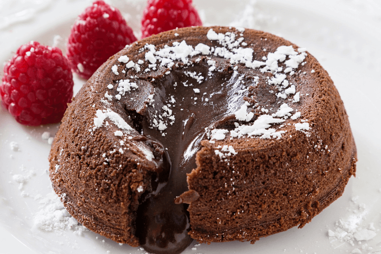 Chocolate oozing out from lava cake and served with 3 raspberries